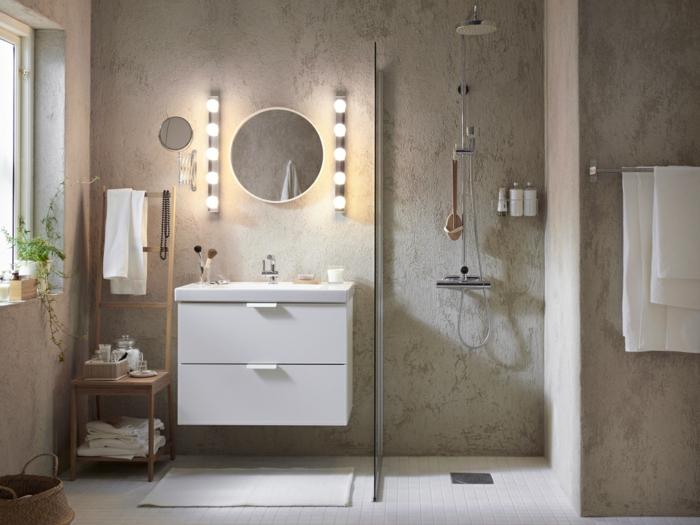 salle de bain italienne aux éléments industriels, miroir rond, meuble de rangement de serviettes et accessoires, appliques murales originales, enduit béton