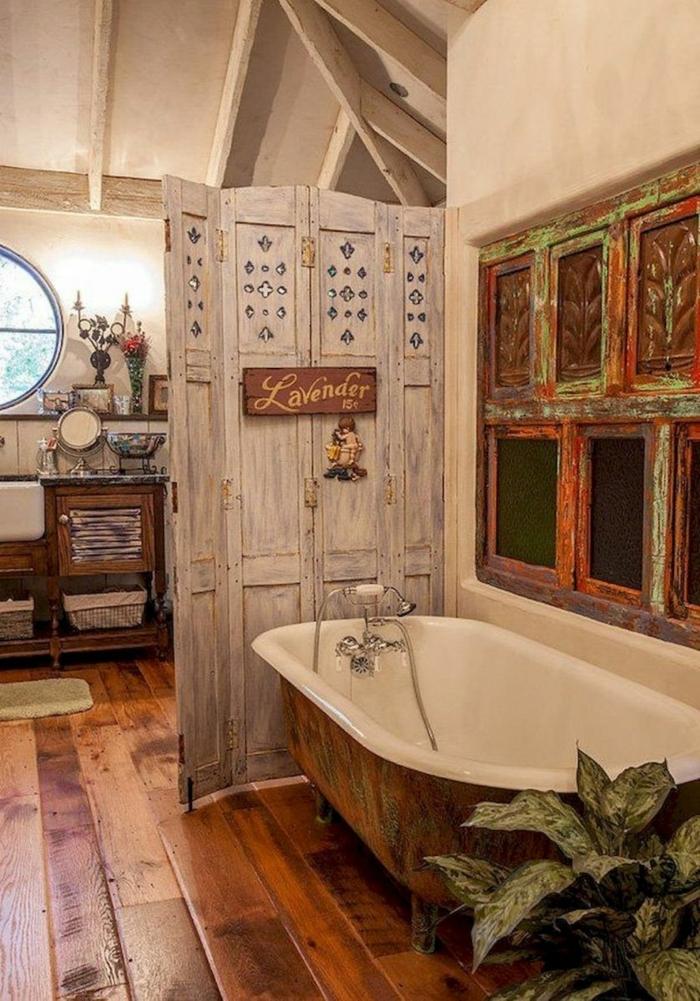 grande baignoire ancienne, sol en planches de bois laquées, paravent en bois rétro, poutres apparentes, grande plante