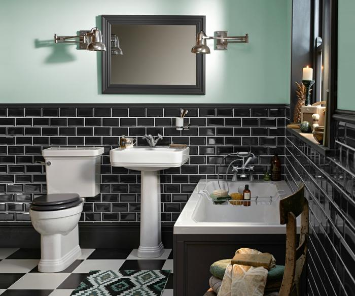 carrelage métro noir, carreaux noirs et blancs au sol, lavabo colonne, baignoire rectangulaire, chaise en bois vintage, appliques industrielles