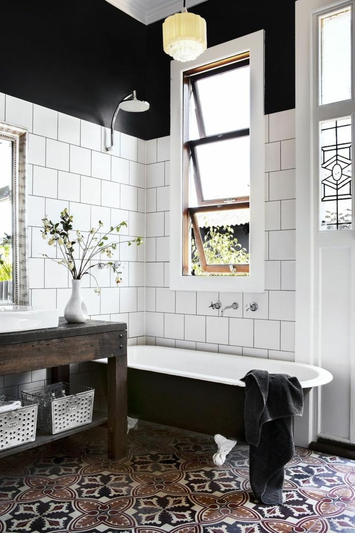 déco de salle de bain en noir et blanc, baignoire en fonte noire et blanche, carreaux blancs et sol carreaux de ciment; murs noirs