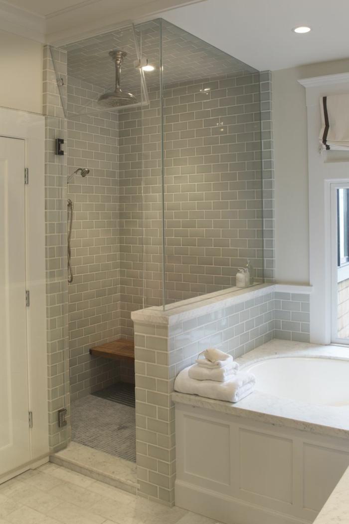 intérieur de salle de bain gris, banquette de salle de bain suspendue en bois, douche montée au plafond, mur carreaux métro et cloison transparente