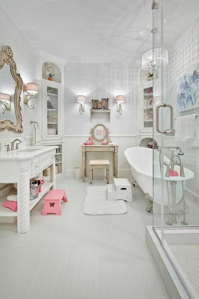 salle de bain toute blanche aux accents roses, baignoire ovale, robinet chromé, tapis blanc, table console ancienne, miroir baroque, appliques roses
