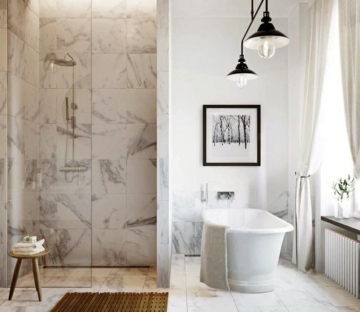 salle de bain avec une douche à l'italienne, petit tabouret en bois, baignoire blanche, lampes industrielles, cadre peinture monochrome, carreaux imitation marbre