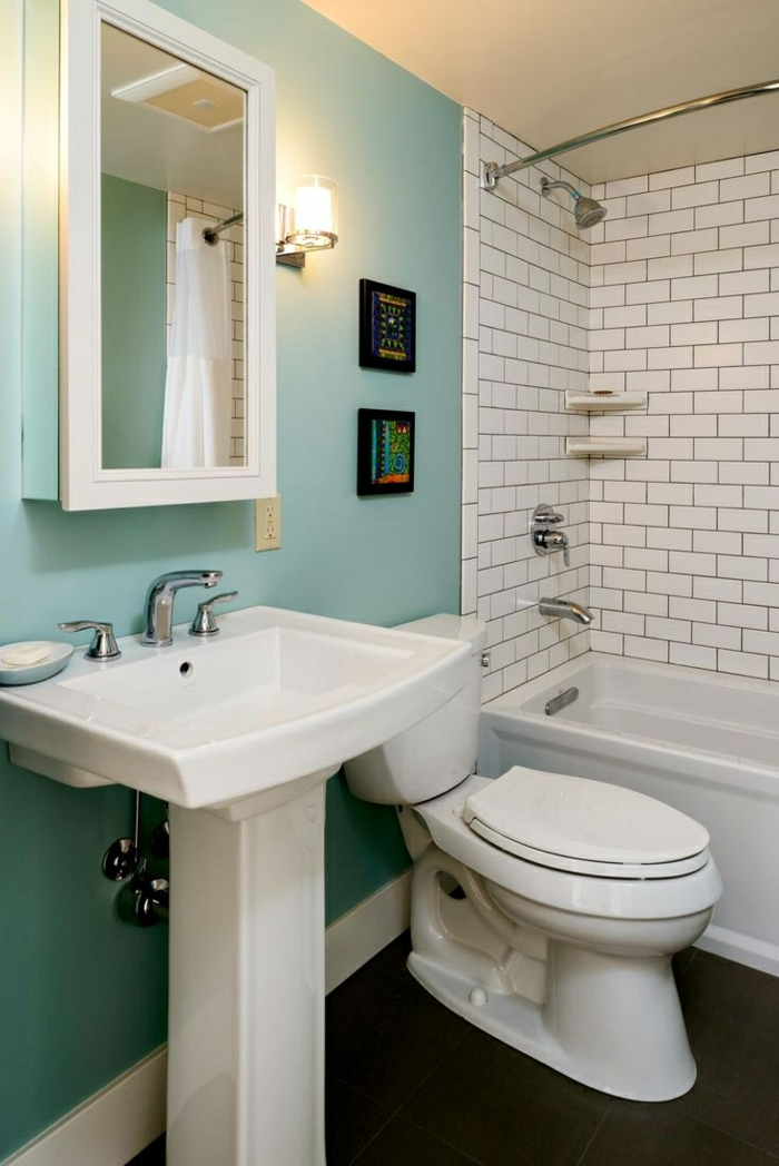 aménager une petite salle de bain, mur bleu, carreaux métro, petites peintures abstraites, baignoire rectangulaire