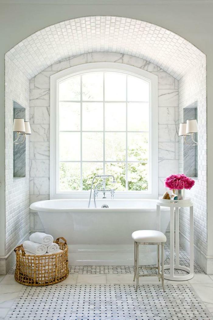 salle de bain blanche, panier tressé, petit tabouret, table ronde haute, bouquet fleurs roses, porte-fenêtre arquée, carrelage vintage