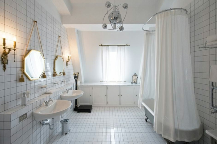 salle de bain toute blanche, miroirs octogonaux au cadre doré, carreaux blancs, lavabo rétro blanc, baignoire ancienne