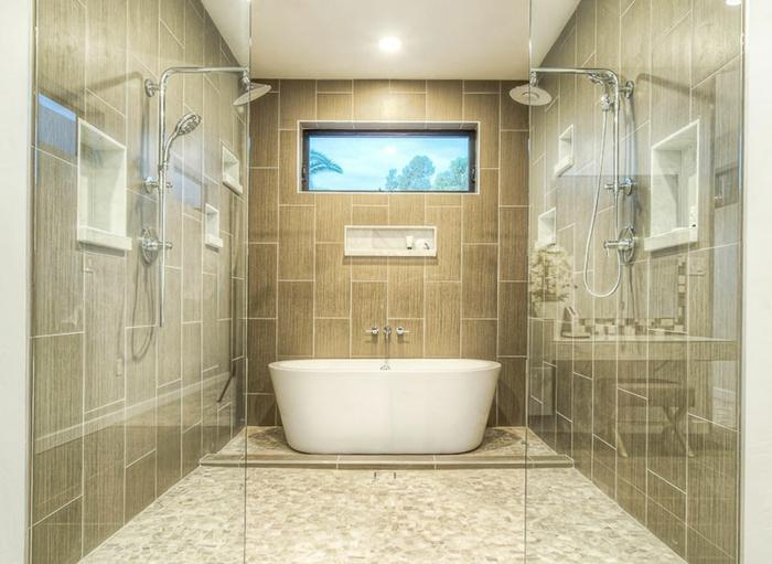 baignoire blanche, sol beige en petites tuiles, deux douches à l'italienne, espace pratique et commode