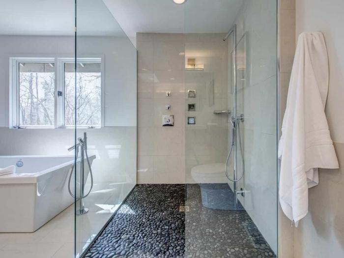 douche plain pied sol galets noirs, ambiance spa, salle de bain lumineuse, grande baignoire, carreaux muraux lisses, fenêtre