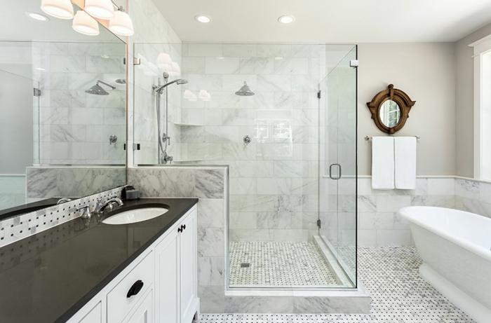 salle de bain blanche avec une grande cabine de douche, petites tuiles au sol, miroir géant, miroir rond cadre décoratif