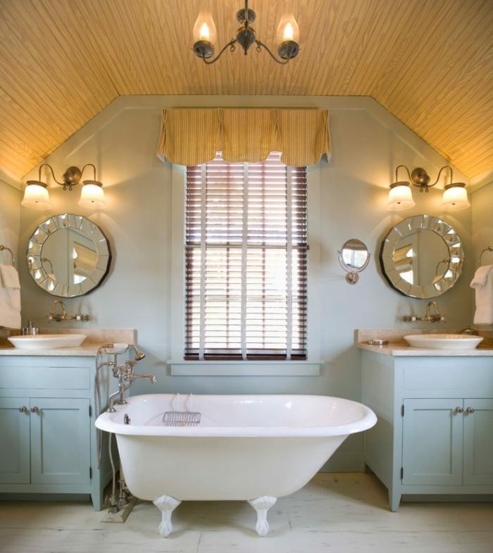 baignoire asymétrique, miroirs ronds art déco, deux lavabos et meubles sous lavabo bleus, plafond en pente