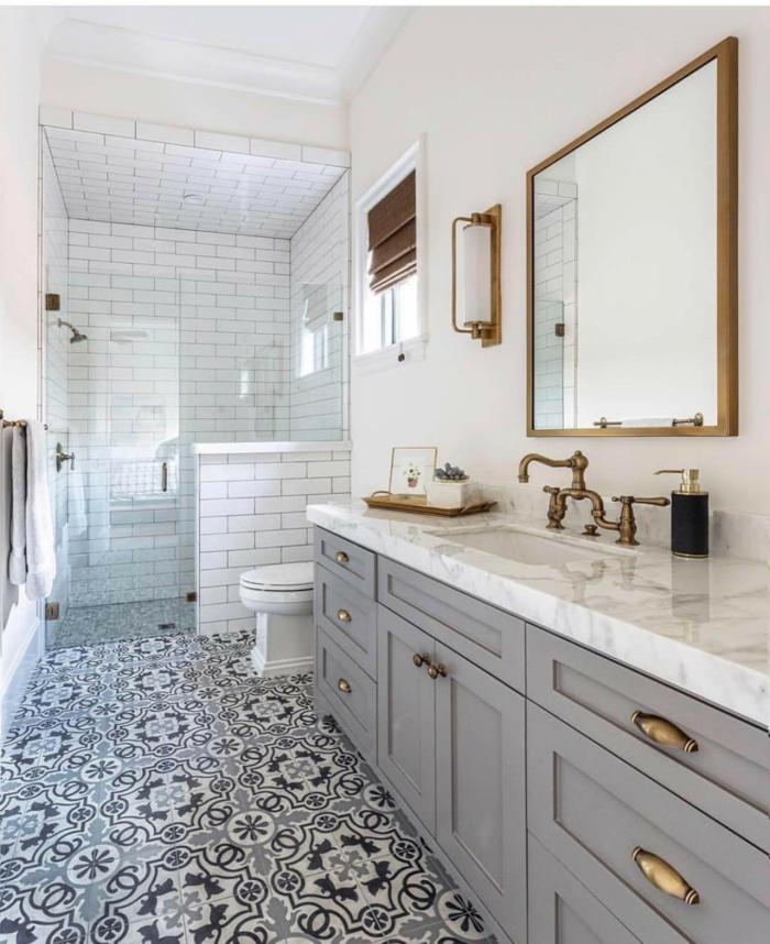 salle de bain en blanc et gris, motifs carreaux de ciment, douche plain pied, cadre de miroir cuivré, robinet cuivré vintage