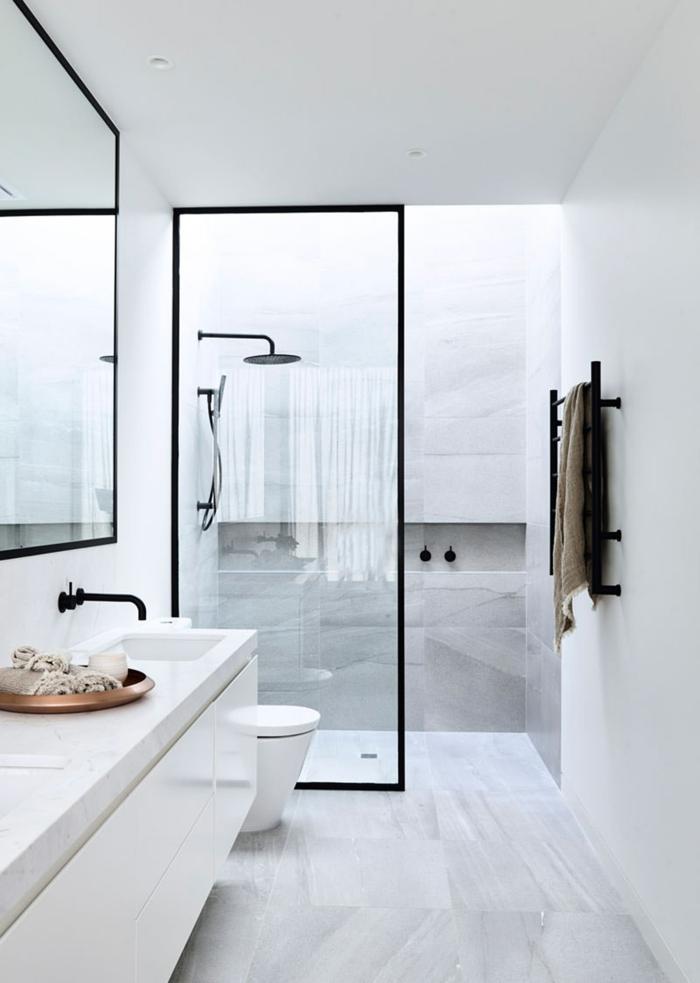 salle de bain au design sobre, tête de douche ronde, vasque blanche minimaliste, plateau cuivré rond, cloison verrière profilé noir