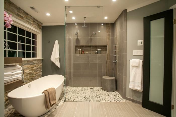 baignoire ovale blanche, sol sous la douche en galets blancs, rangement intégré, revêtement mural pierres, sol en bois, tabouret de douche
