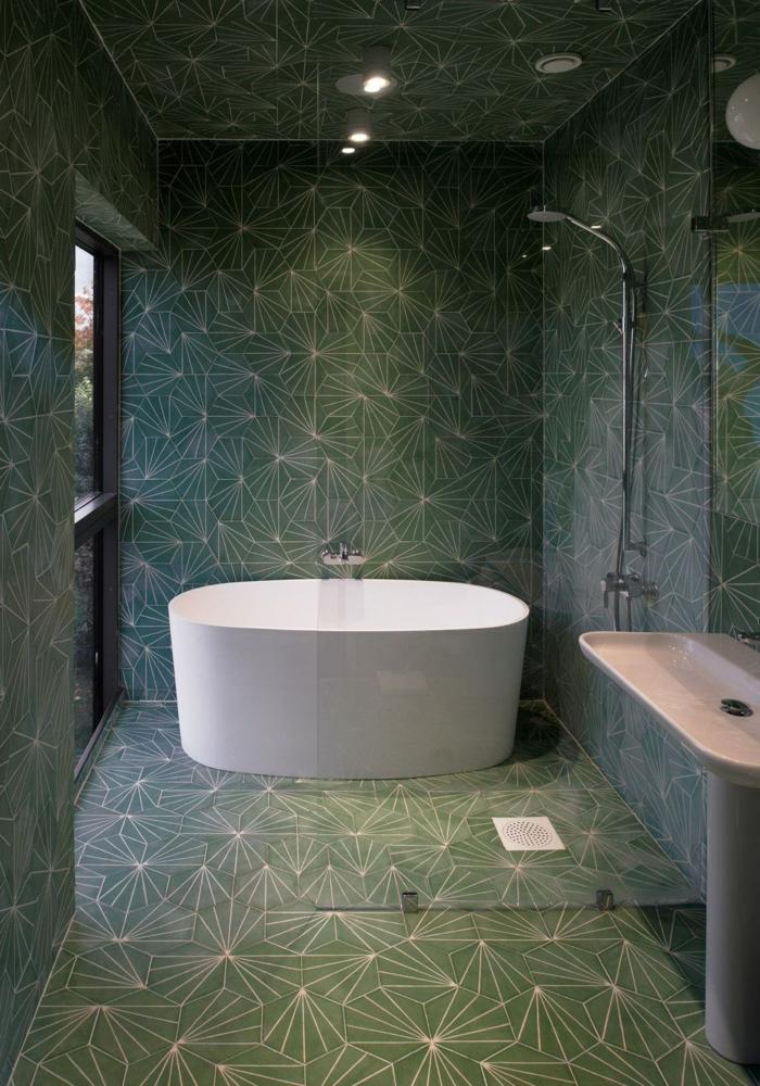 baignoire blanche îlot, carreaux verts aux motifs graphiques blancs, lavabo colonne vintage, spots au plafond