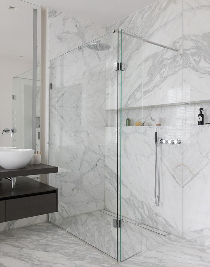 salle de bain zen sur petite surface, meuble sous vasque suspendu, petite vasque ronde, rangement intégré, carreaux marbrés blancs