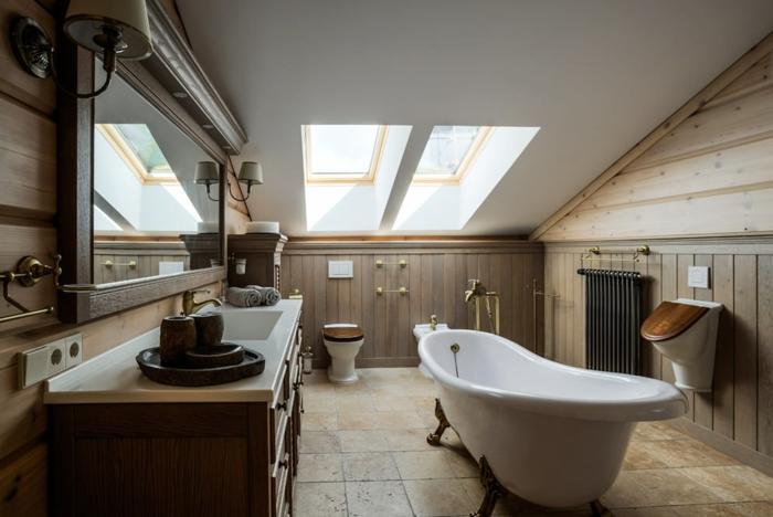 baignoire blanche, grand meuble sous vasque, miroir encadré, murs en bois, salle de bain mansardée, fenêtre de toit