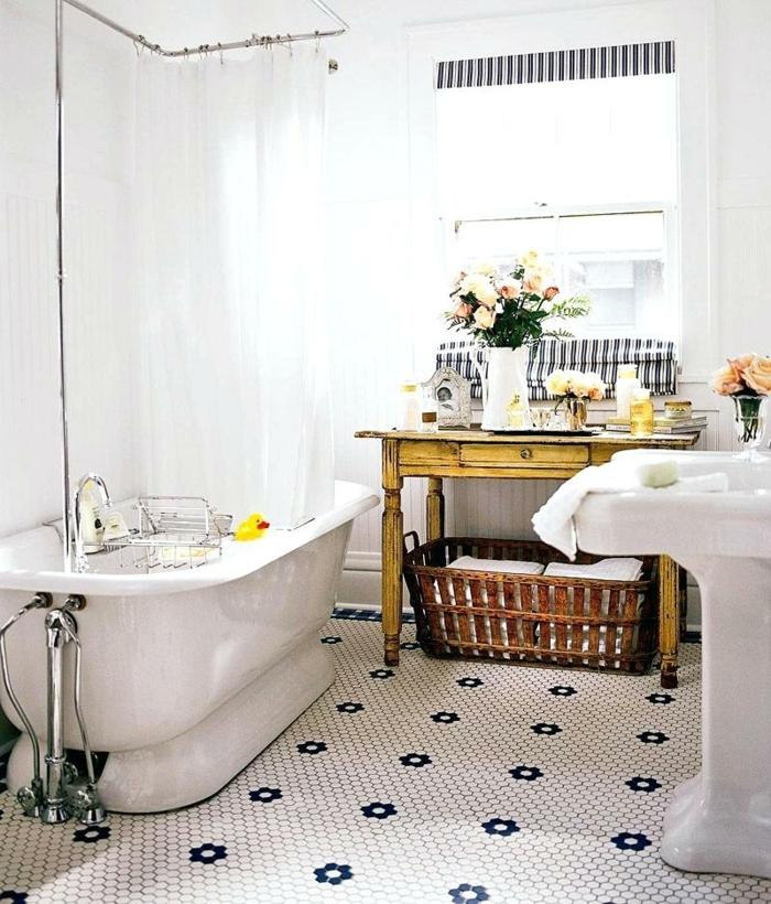 carrelage aux motifs originaux, baignoire blanche, grand panier rustique, bureau vintage recyclé, vasque colonne sur pied