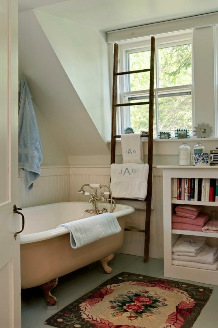 petit tapis aux motifs floraux, baignoire pastel, robinet chromé, échelle en bois, petit meuble de rangement avec livres et serviettes
