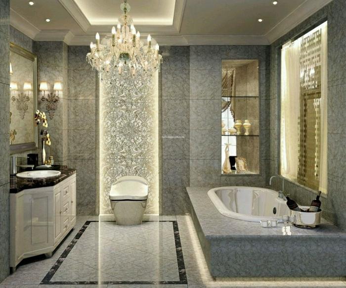 salle de bain esprit industriel, plafonnier baroque, baignoire à encastrer, carrelage de luxe gris clair, faux plafond éclairé et rangement intégré