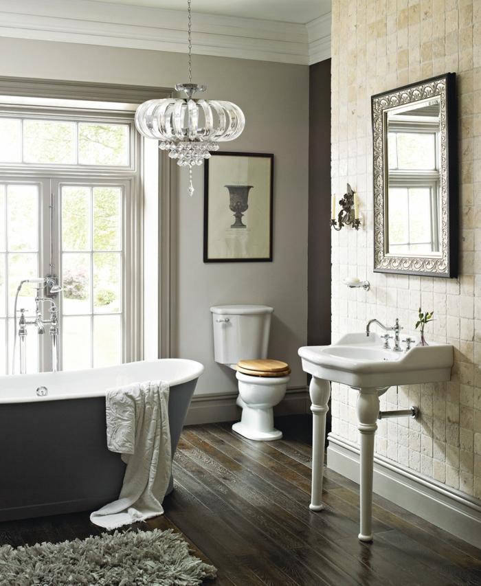 plafonnier en cristal, grande baignoire en gris et blanc, vasque vintage blanche, sol en parquet foncé, miroir rectangulaire au cadre, salle de bain imposante