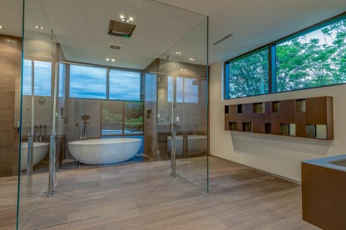 salle de bain élégante, carreaux travertin, grandes fenêtres panoramiques, baignoire blanche ovale, cloisons en verre
