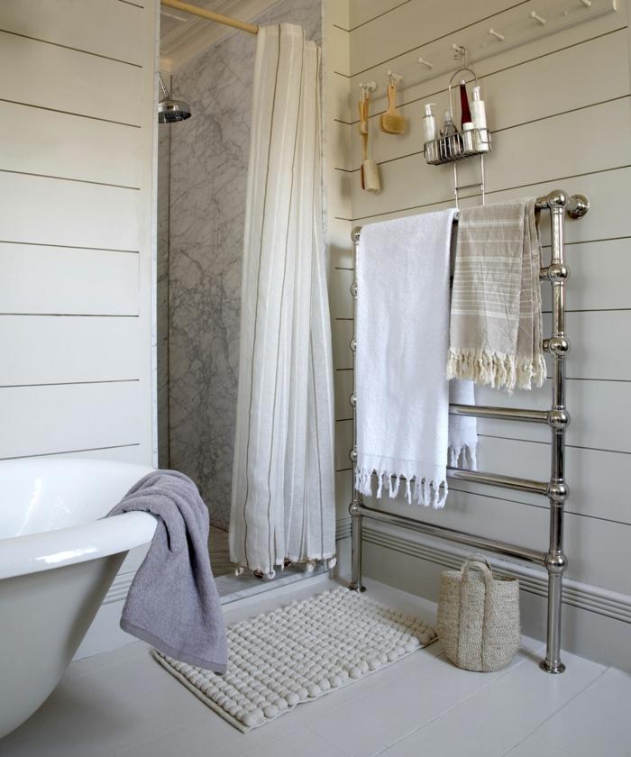 baignoire îlot et douche avec cloison blanche, rideau blanc, porte serviette chromé, tapis antidérapant et panier en fibres naturels