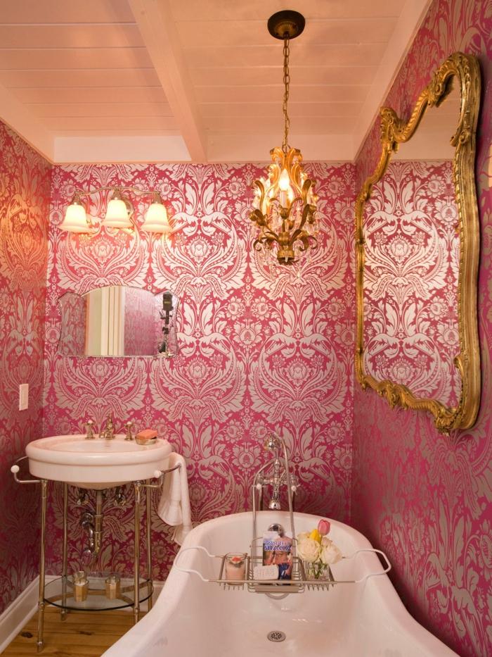 baignoire blanche, papier peint rose baroque, miroir cadre baroque et luminaire suspendu, vasque ronde; petit miroir décoratif