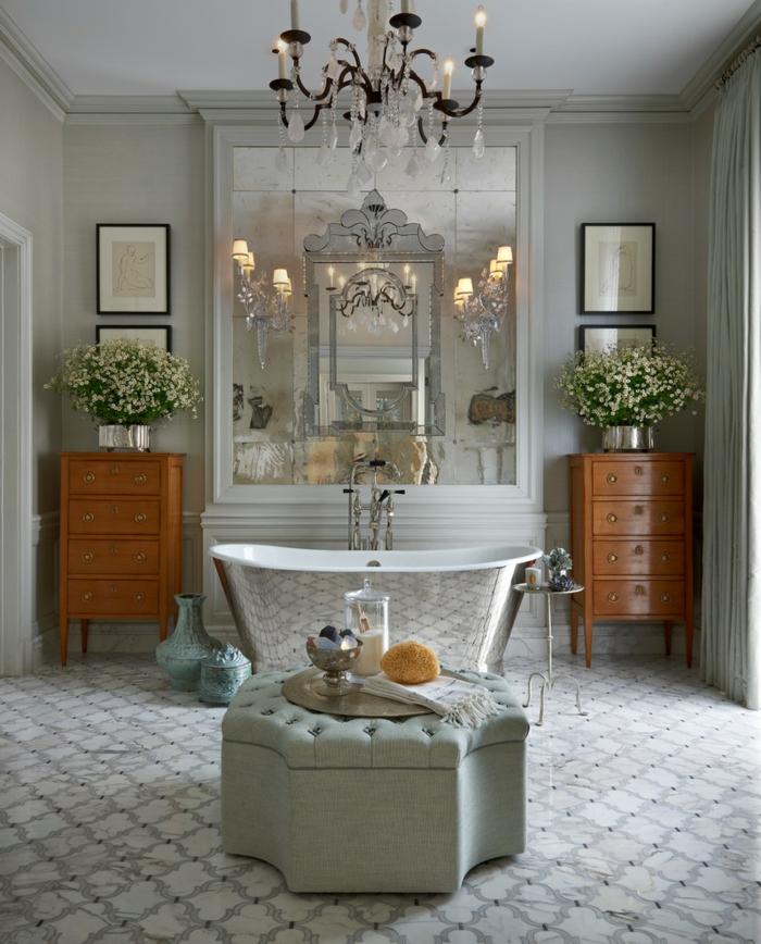 ottoman gris capitonné, baignoire couleur argent, appliques élégantes, meubles en bois laqué, grand miroir rectangulaire