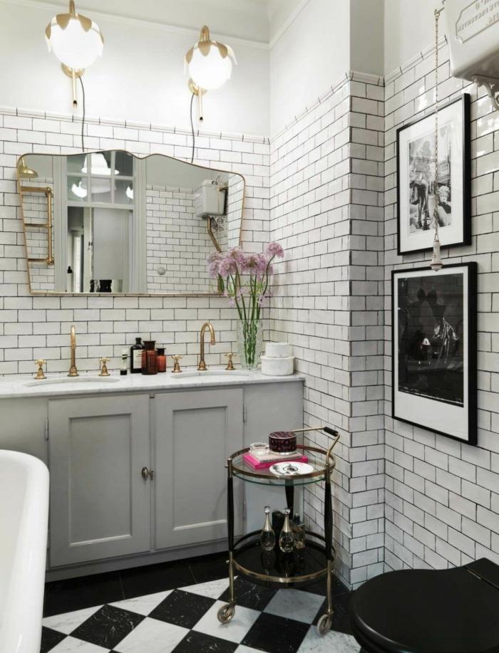 sol aux carreaux en noir et blanc, grandes appliques murales, carreaux métro, miroir pop art, deux petites lavabos, photos monochromes