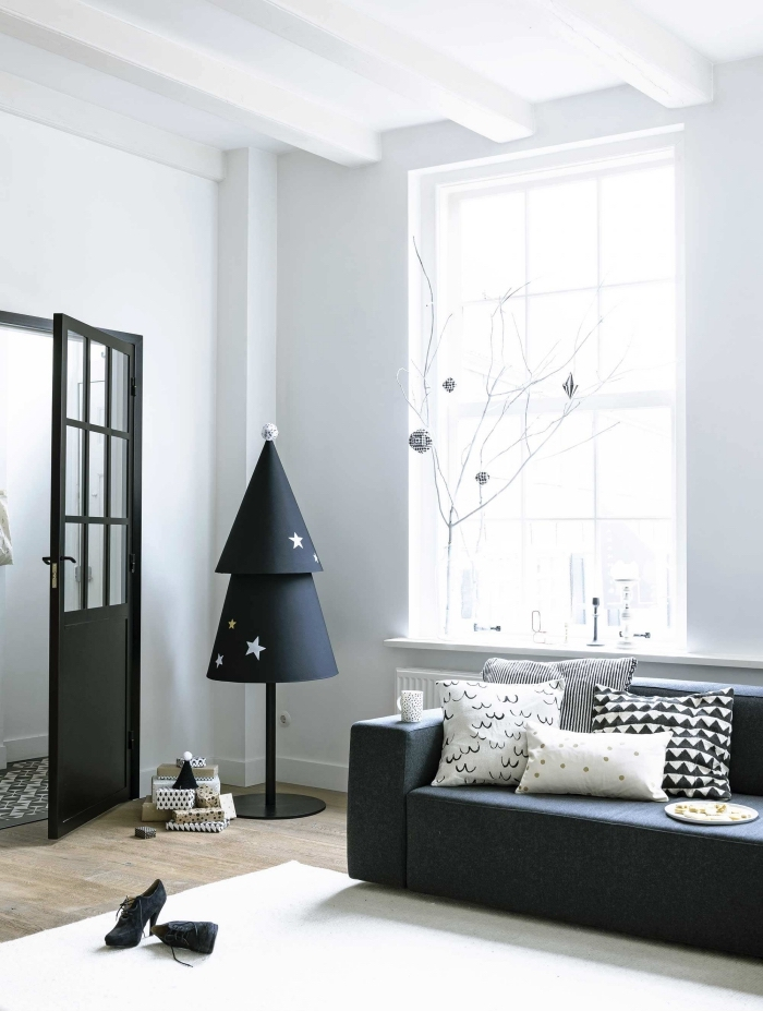sapin original en cônes de papier et un piétement en métal noir qui s'harmonise avec le décor minimaliste scandinave en noir et blanc