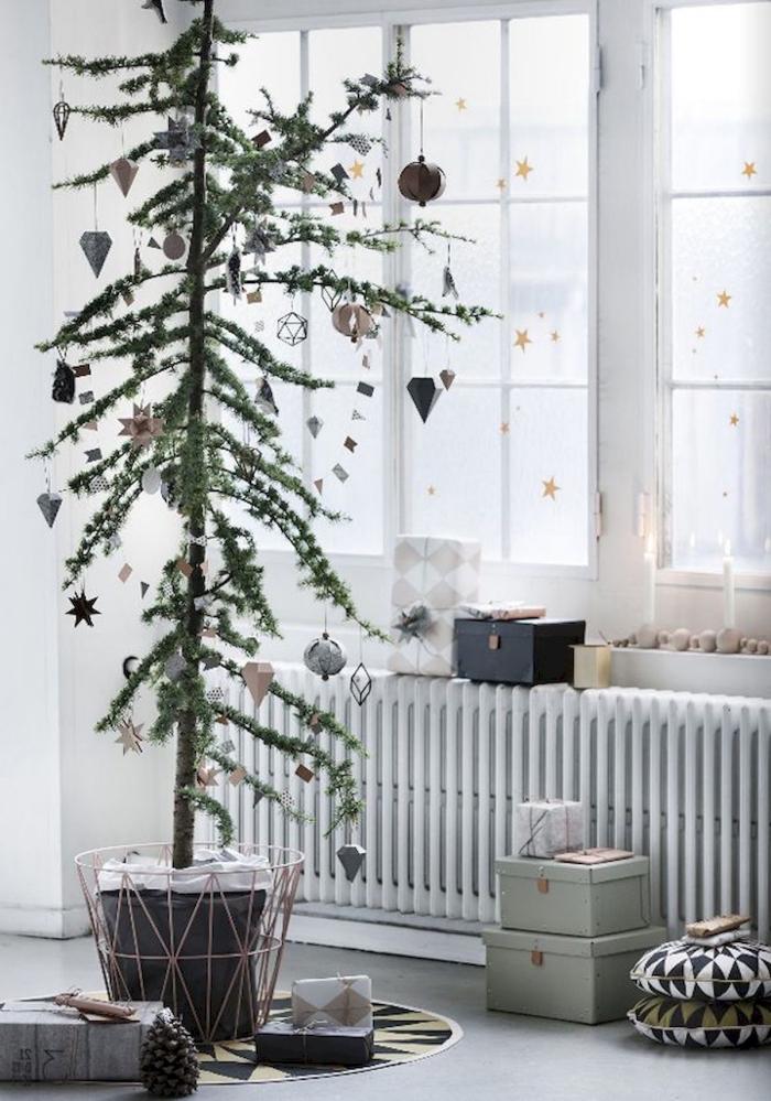 des stickers petites étoiles dorées qui ornent les vitres du salon scandinave blanc, déco de noël minimaliste scandinave avec un arbre de noël vert en pot agrémenté d'ornements vintage