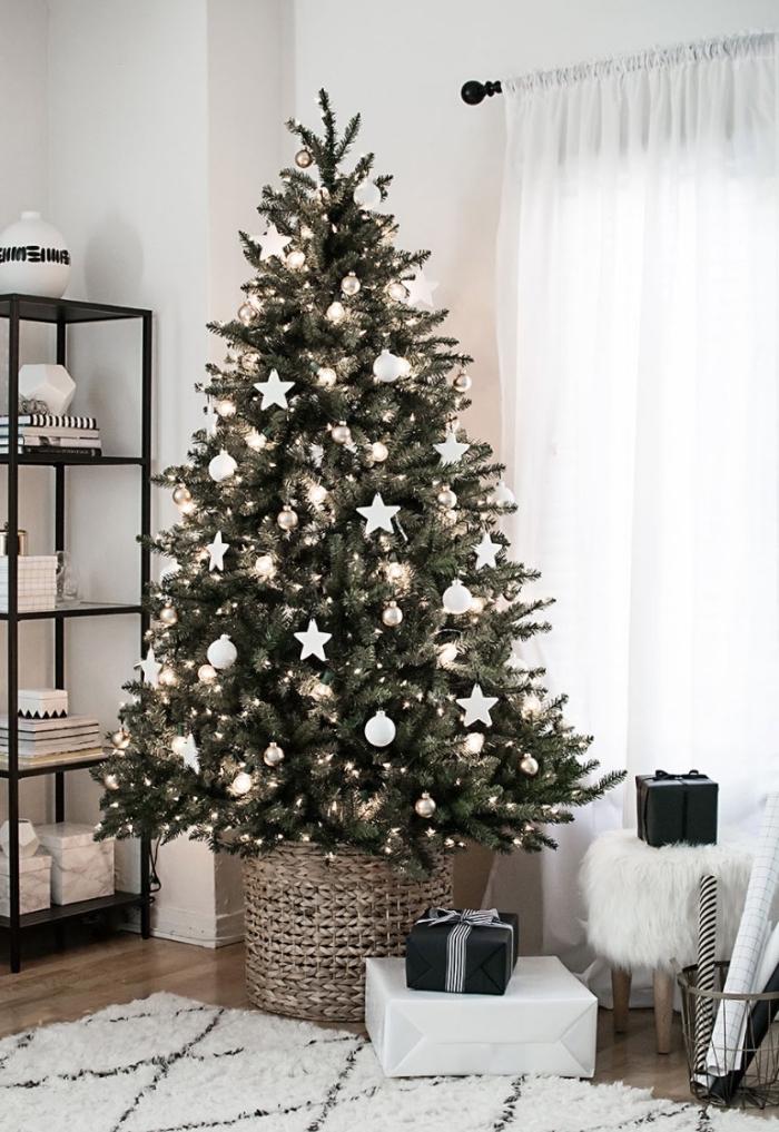 un sapin de noel naturel décoré dans un style minimaliste scandinave avec des ornements de noel blancs, posé dans un panier en rotin, salon nordique en blanc et noir
