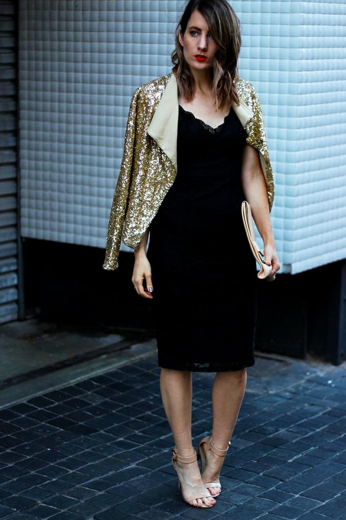 femme habillée pour une soirée officielle, veston pailleté, robe moulante noire, mi-longue, décolleté en triangle, sandales haut talon
