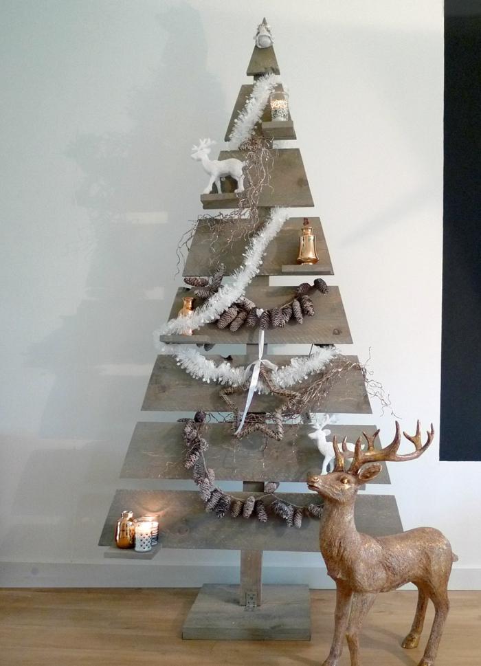 sapin en planches de bois, guirlandes blanches, guirlandes de pommes de pin, statuette de cerf, bougies et petites bouteilles sur les étagères du sapin