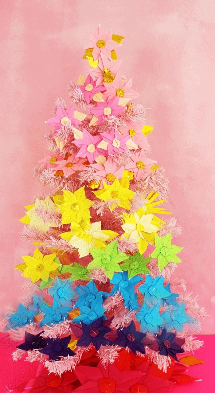 sapin de noël artificiel rose pastel orné de poinsettias multicolores réalisés en papier