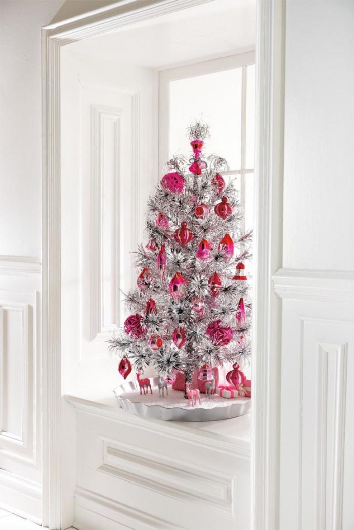 joli sapin de noël artificiel original argent métallisé décoré avec des ornements de noël vintage rose, posé sur le rebord de fenêtre, deco fenetre noel original