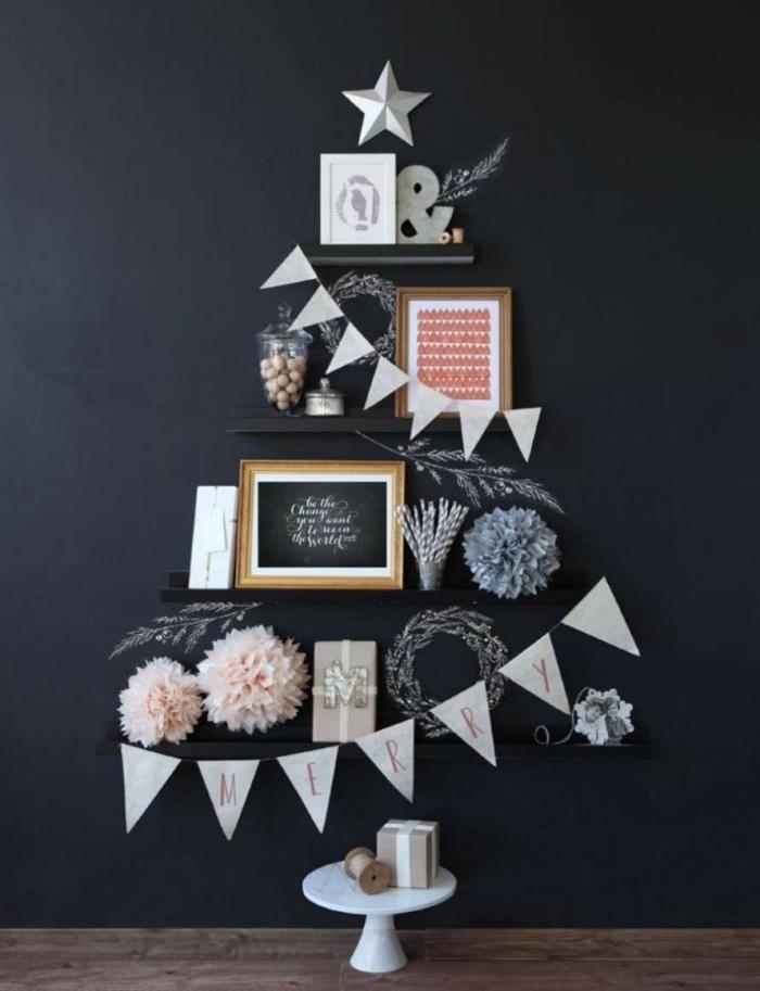 des étagères noires sur un fond noir décorées avec des petits objets déco aux tons du gris et du rose dont la composition ressemble à la forme d'un arbre de noel