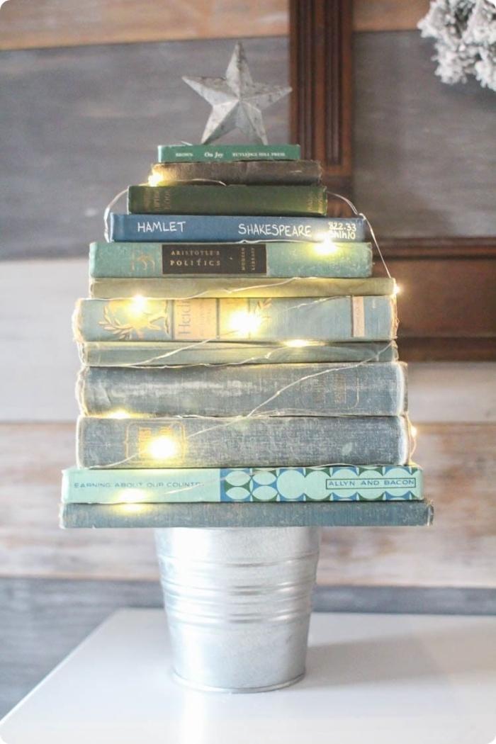 un tas de livres à couvertures vintage posé sur un seau en zinc et entouré d'une guirlande lumineuse, sapin décoratif insolite en livres