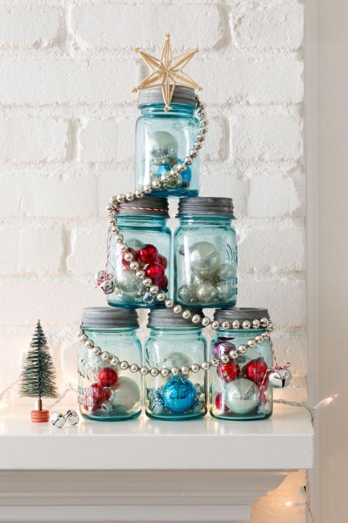 une alternative originale à l'arbre de noël classique, des bocaux en verre couleur bleu empilés pour en former un sapin original