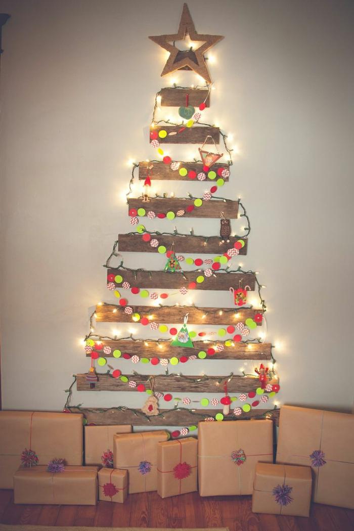 planches de vieilles palettes fixées au mur, étoile, guirlande de lampes lumineuses, guirlande de pompons multicolores, paquets cadeaux