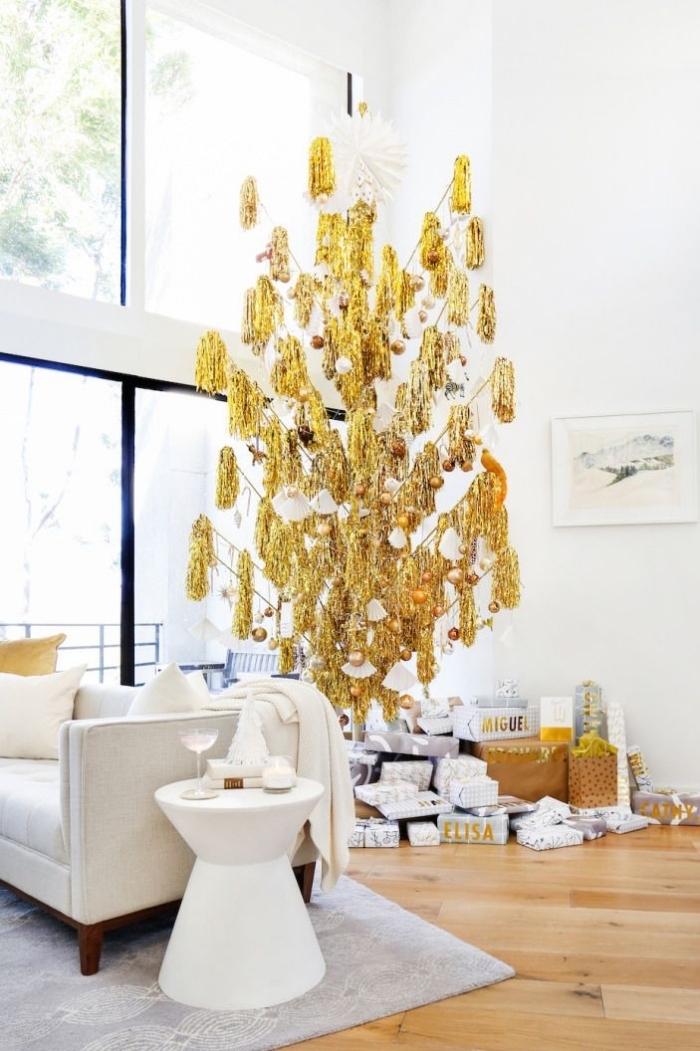 sapin de noe artificiel de luxe à franges dorées, posé à l'envers et suspendu au plafond dans un salon moderne en bla