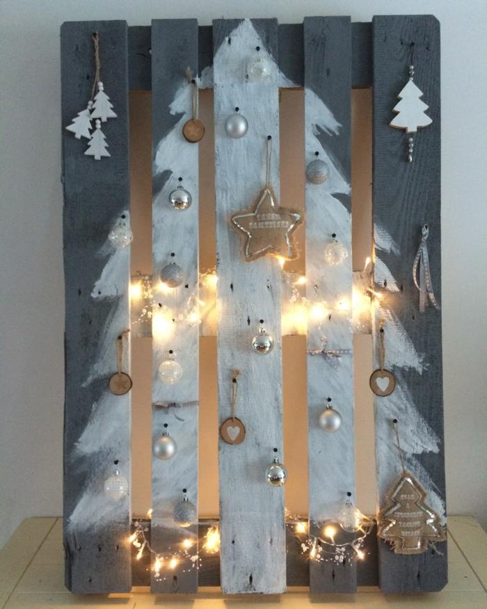 sapin de noel blanc peint sur une palette, petits sapins décoratifs, ornements de sapin accrochés aux planches de la palette