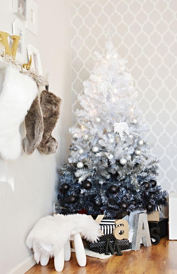 sapin de noel en blanc, gris et noir déposé dans l'angle de la pièce, orné de boules de noël blanc et noir mat, arbre de noël artificiel dans un dégradé de couleurs blanc et noir