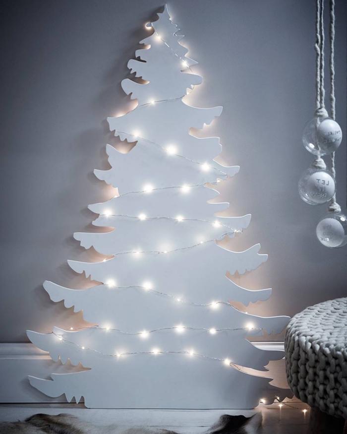 décor de noël romantique et poétique tout en blanc, sapin de noel blanc découpé dans une planche de bois et éclairé par les petites lueurs de la guirlande