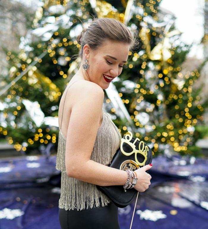 sac à main original, éléments métalliques dorés, boucles d'oreilles en argent, bracelets et montre élégante, débardeur gris clair aux franges, grand sapin de noel