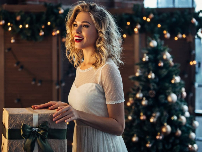 Tenue de noël pour femme, robe pour les fetes de fin d année, femme jolie qui porte une robe blanche courte à manche dentelle