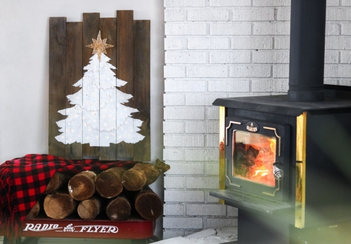 sapin de noel en bois a faire soi meme à partir d'une palette de bois récupérée, sapin en peinture blanche sur un tableau en bois récup posé à côté de la cheminée, dans un décor rustique