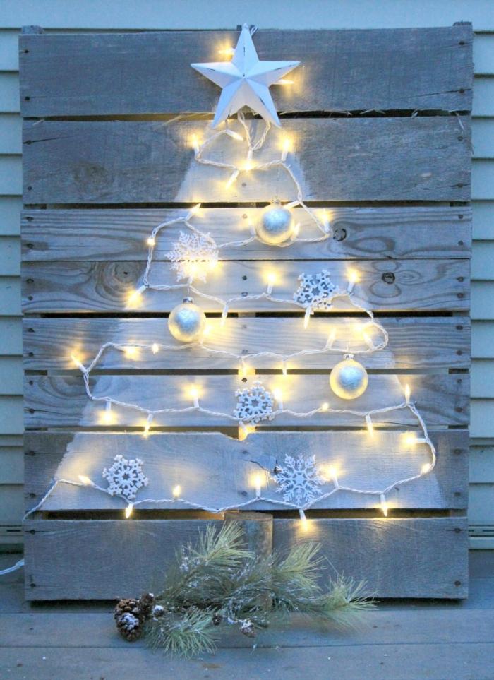 déco de noel miraculeuse réalisée sur une palette de bois en blanc, guirlande d'ampoules blanche, brin de pin