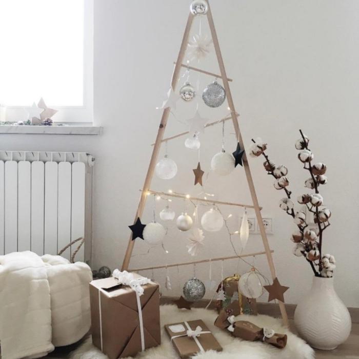 structure en bois légère et aérienne en forme de triangle décorée avec des suspensions de noël traditionnelles façon un véritable arbre de noël