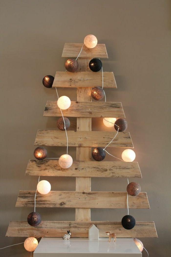 déco de noel scandinave avec guirlande en boules et ficelle, boules de noel lumineuses et sapin en planches